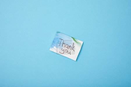 greeting card with thank you lettering on blue background with copy space
