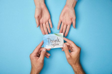 Photo pour Vue recadrée de l'homme donnant la carte de voeux avec le lettrage de remerciement à la femme sur le fond bleu - image libre de droit