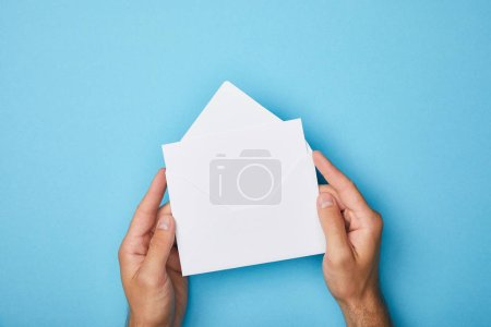 Foto de Vista recortada del hombre sosteniendo sobre con tarjeta blanca en blanco sobre fondo azul - Imagen libre de derechos