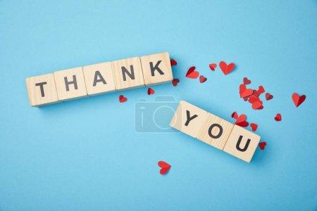 Photo pour Vue de dessus des cubes en bois avec des mots de remerciement et des coeurs en papier rouge sur fond bleu - image libre de droit