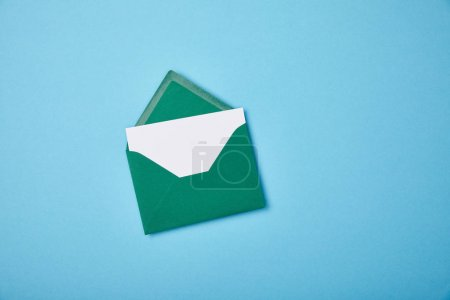 Photo for Green envelope with blank white card on blue background - Royalty Free Image