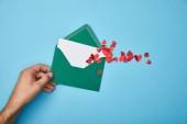 """Постер, картина, фотообои """"обрезанный вид человека, держащего зеленый конверт с пустой белой картой и бумагой вырезать красные сердца на синем фоне"""""""