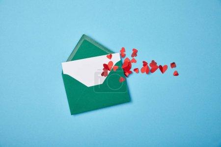 Foto de Sobre verde con tarjeta blanca en blanco y corazones de papel rojo sobre fondo azul - Imagen libre de derechos