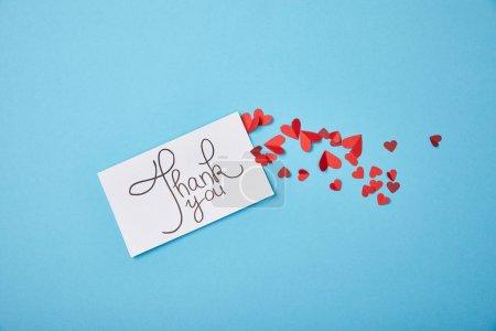 Photo pour Carte blanche avec lettrage de remerciements et coeurs en papier rouge sur fond bleu - image libre de droit