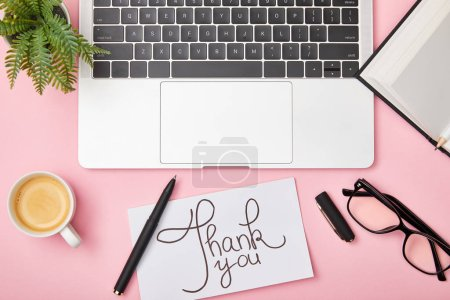 top view of laptop, green plant, coffee, notebook, glasses and card with thank you lettering at workplace on pink background