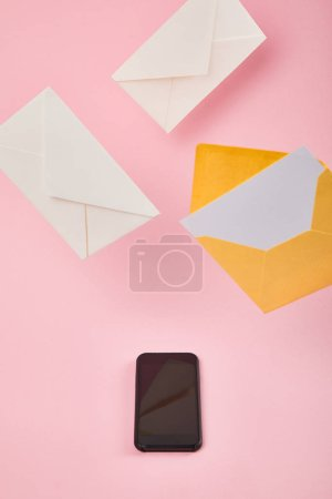 Photo for Envelopes near smartphone with blank screen on pink background - Royalty Free Image