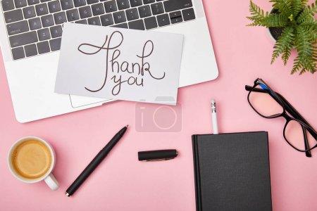 Photo pour Vue supérieure de l'ordinateur portatif, de la plante verte, du café, du cahier, des glaces et de la carte avec le lettrage de remerciement sur le fond rose - image libre de droit