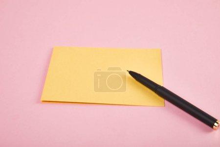 Photo pour Enveloppe jaune avec le stylo sur le fond rose - image libre de droit