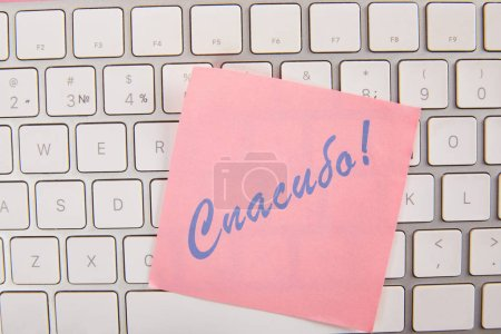 top view of pink sticky note with thankful lettering in russian on laptop keyboard