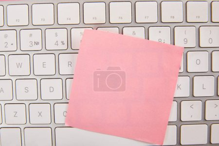 Photo for Top view of empty pink sticky note on laptop keyboard - Royalty Free Image