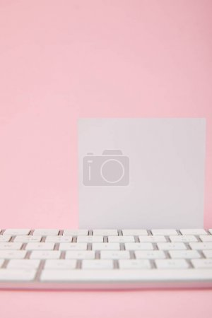 Foto de Vista de cerca de la tarjeta blanca en blanco cerca del teclado de la computadora sobre fondo rosa - Imagen libre de derechos