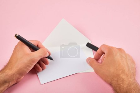 Photo pour Vue recadrée de l'homme écrivant avec stylo sur carte blanche vide près de l'enveloppe sur fond rose - image libre de droit