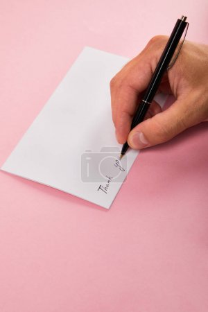 partial view of man writing with pen thank you lettering on white card on pink background