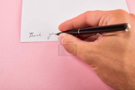 przycięte widok człowieka piśmie z długopisem dziękuję napis na białej karcie na różowym tle
