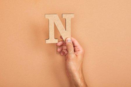 Photo pour Vue recadrée de l'homme retenant la lettre coupée de papier N sur le fond beige - image libre de droit