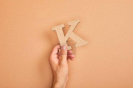 Photo pour Vue partielle de l'homme retenant la lettre coupée de papier K sur le fond beige - image libre de droit