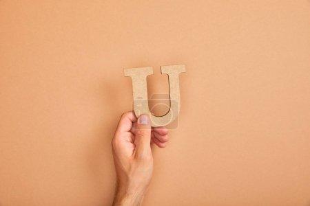 Photo pour Vue recadrée de main mâle retenant la lettre coupée de papier U sur le fond beige - image libre de droit