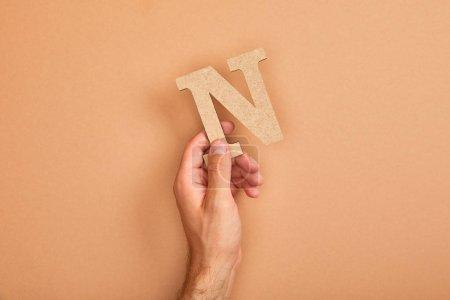 Photo pour Vue partielle de l'homme retenant la lettre coupée de papier N sur le fond beige - image libre de droit