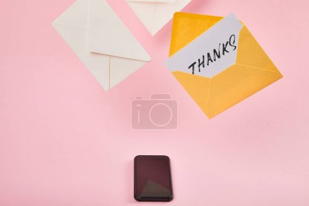 yellow envelope with white card with thanks lettering near letters and smartphone with blank screen on pink background