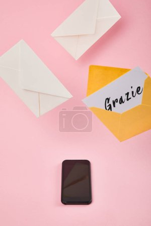 Photo for Yellow envelope with white card with grazie lettering near letters and smartphone with blank screen on pink background - Royalty Free Image