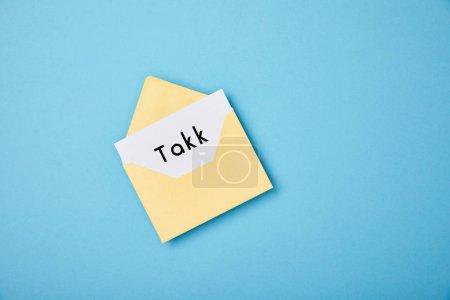 Photo pour Enveloppe jaune et carte blanche avec le mot de takk sur le fond bleu - image libre de droit