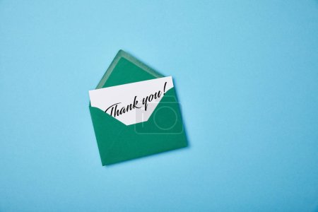 Photo for Green envelope and white card with thank you letting on blue background - Royalty Free Image