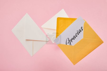 Photo for Yellow bright envelope with gracias lettering on white card near letters on pink background - Royalty Free Image