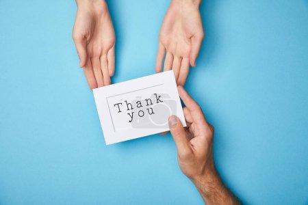 Photo pour Vue recadrée de l'homme donnant la carte blanche dans le cadre avec le lettrage de remerciement à la femme sur le fond bleu - image libre de droit