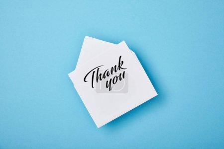 Photo pour Enveloppe avec le lettrage de remerciement sur la carte blanche sur le fond bleu - image libre de droit
