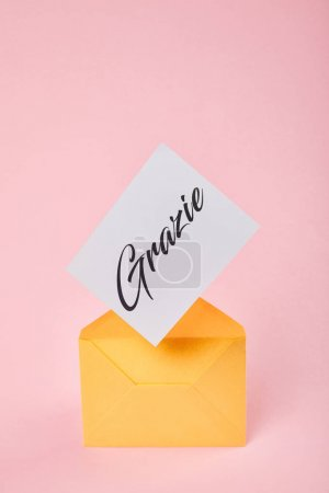 yellow envelope with grazie word on white card on pink background