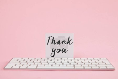 Photo pour Carte blanche avec le lettrage de remerciement près du clavier d'ordinateur sur le fond rose - image libre de droit