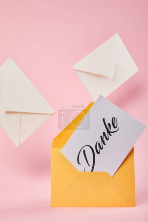 Photo pour Enveloppe jaune avec mot danke sur carte blanche près des lettres sur fond rose - image libre de droit