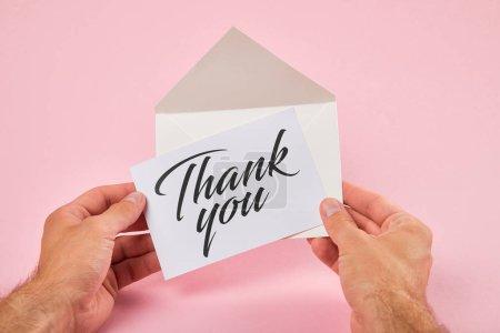 Photo pour Vue recadrée de l'enveloppe de fixation d'homme avec le lettrage de remerciement sur la carte blanche sur le fond rose - image libre de droit
