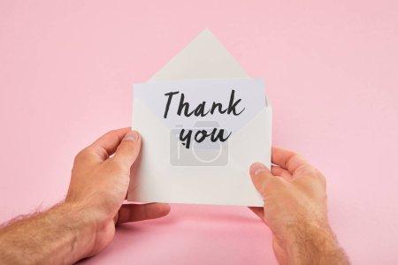 Photo pour Vue recadrée de l'enveloppe de fixation d'homme et de la carte blanche avec des mots de remerciement sur le fond rose - image libre de droit