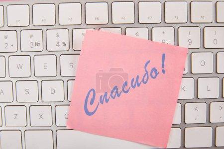Photo pour Vue supérieure de la note collante rose avec le lettrage reconnaissant en langue russe sur le clavier d'ordinateur portatif - image libre de droit