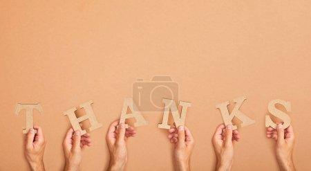 Photo pour Vue partielle des hommes retenant le mot remerciat arrangé des lettres coupées de papier sur le fond beige - image libre de droit