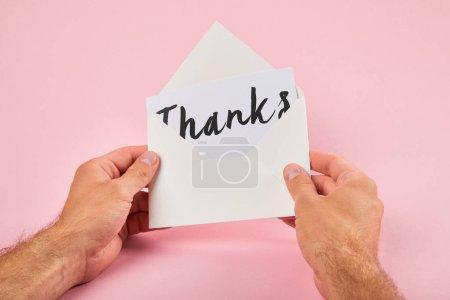 Photo pour Vue recadrée de l'homme tenant enveloppe et carte blanche avec mot de remerciement sur fond rose - image libre de droit