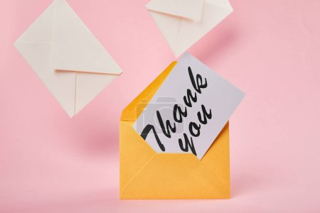 Photo for Yellow envelope with thank you lettering on white card near letters on pink background - Royalty Free Image