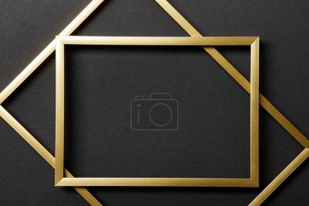 Foto de Vista superior de marcos dorados vacíos sobre fondo negro - Imagen libre de derechos