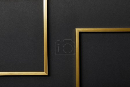 top view of empty golden frames on black background with copy space