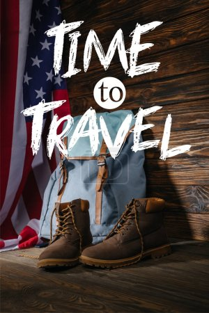 Photo for Trekking boots, backpack and american flag on wooden surface with time to travel illustration - Royalty Free Image