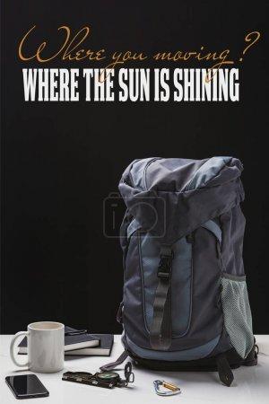 Foto de Mochila, taza, cuadernos, teléfono inteligente y equipo de trekking aislado en negro con donde se mueve la pregunta y donde el sol está brillando respuesta - Imagen libre de derechos