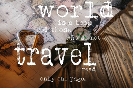 Photo for Compass, safety hook and map on wooden table with the world is a book and those who do not travel read only one page lettering - Royalty Free Image