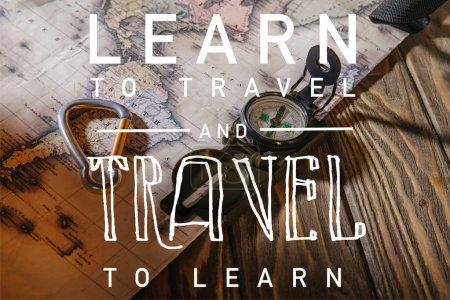 Photo pour Boussole, crochet de sécurité et carte sur la table en bois avec apprendre à voyager et voyager pour apprendre l'illustration - image libre de droit