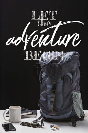 Photo pour Sac à dos, tasse, cahiers, smartphone et équipement de trekking isolés sur le noir avec laisser l'aventure commencer le lettrage - image libre de droit