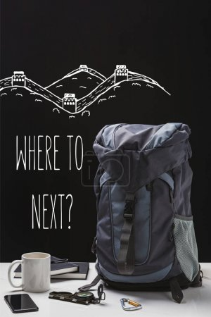 Photo for Backpack, cup, notebooks, smartphone and trekking equipment isolated on black with where to next question - Royalty Free Image