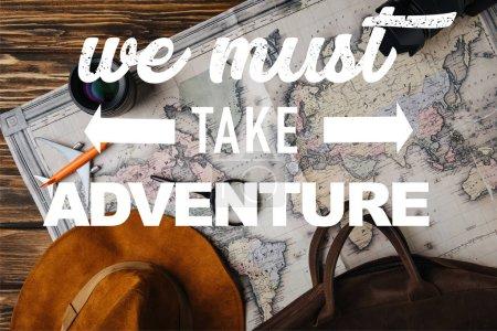 Photo pour Vue supérieure du sac en cuir brun, chapeau, loupe, plan modèle, appareil photo et objectif sur la carte avec nous devons prendre l'illustration d'aventure - image libre de droit