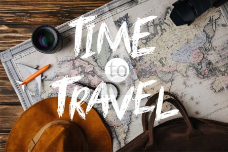 Photo pour Vue supérieure du sac en cuir brun, chapeau, loupe, plan modèle, appareil photo et objectif sur la carte avec le temps d'illustration de voyage - image libre de droit