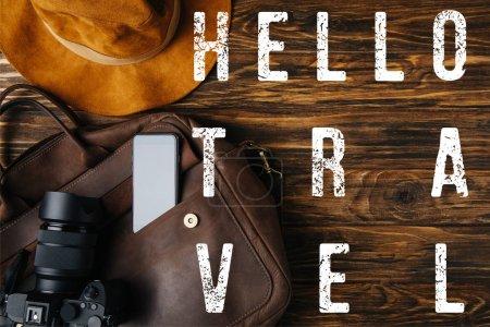 Foto de Vista superior de la bolsa de cuero marrón, sombrero, cámara digital y teléfono inteligente en la mesa de madera con hola ilustración de viaje - Imagen libre de derechos