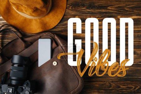 Foto de Vista superior de la bolsa de cuero marrón, sombrero, cámara digital y teléfono inteligente en la mesa de madera con buena ilustración de vibraciones - Imagen libre de derechos